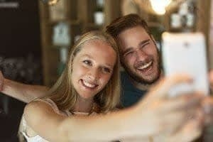 Couple taking a selfie showing the results of cosmetic dentistry teeth whitening received at State of the Art Dental Group in Rockville, MD.